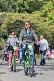 Turister på uthyrnings- cyklar i solbelysta Vondelpark, Amsterdam, Nederländerna Arkivfoto