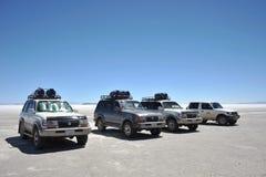 Turister på Uyunien saltar lägenheter som torkas upp den salta sjön i Altiplano arkivfoto