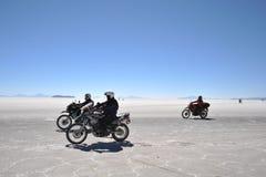 Turister på Uyunien saltar lägenheter som torkas upp den salta sjön i Altiplano Royaltyfri Fotografi