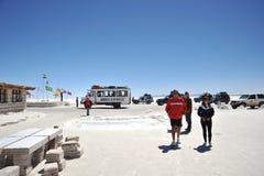 Turister på Uyunien saltar lägenheter som torkas upp den salta sjön i Altiplano Arkivfoton