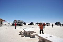 Turister på Uyunien saltar lägenheter som torkas upp den salta sjön i Altiplano Fotografering för Bildbyråer