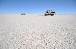 Turister på Uyunien saltar lägenheter som torkas upp den salta sjön i Altiplano Royaltyfria Foton