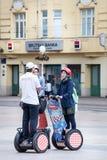 Turister på Segways och turnerar stadshandboken Royaltyfria Bilder