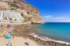 Turister på solen semestrar på den Taurito stranden, Gran Canaria Arkivbild