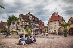 Turister på stadfyrkant i Colmar, Frankrike, Arkivfoton