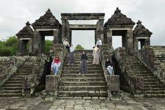 Turister poserar framme av slottporten Ratu Boko Royaltyfri Foto