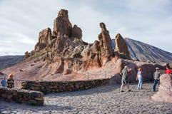 Turister promenerar det beskåda området, mot bakgrunden av djupfryst lava arkivbild