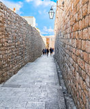 Turister promenerar en gata av den gamla staden Arkivfoto