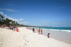 Turister promenerar stranden av den Punta Cana semesterorten Arkivfoto