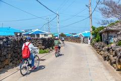 Turister rider en cykel längs gatan på Udo Island, en tur till Sydkorea royaltyfri bild