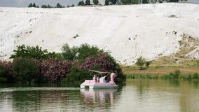 Turister rider ett fartyg i form av en svan på sjön i Pamukkale lager videofilmer