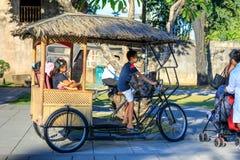 Turister rider på den traditionella trehjulingen för Filippinerna på fortSantiagoträdgården i Intramuros område arkivfoto