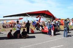 Turister runt om hängning-glidflygplanet på Airshow arkivfoto