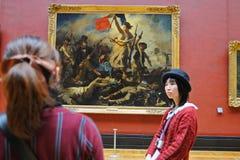 Turister ser målningarna av Eugene Delacroix på Louvremuseet (Musee du Louvre) Royaltyfria Foton