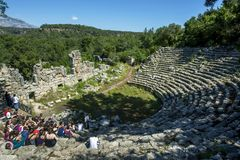 Turister sitter bland fördärvar av teatern på Phaselis i Turkiet Royaltyfri Foto
