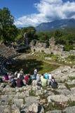 Turister sitter bland fördärvar av teatern på Phaselis i Turkiet Fotografering för Bildbyråer