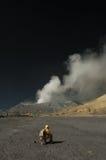 Turister sitter ner framme av det Bromo berget Arkivfoton