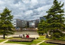Turister sitter på en bänk och en blick i riktningen av den nybyggda Hafencityen i Hamburg arkivfoto