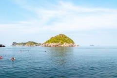Turister snorklar i havet med vaggar med vegetation under härlig blå himmel med moln arkivfoto