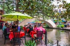 Turister som äter middag på floden, går i afton i San Antonio Texas arkivbilder