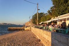 Turister som ?ter och dricker i utomhus- restaurangterrass p? flodstranden royaltyfri foto