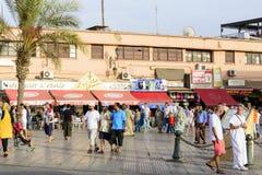 Turister som besöker Djemaa el Fna - marknadsställe i Marrakeshs den medina fjärdedelen på 24 Augusti 2014 i Marrakesh, Marocko Arkivbilder
