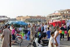 Turister som besöker Djemaa el Fna - marknadsställe i Marrakeshs den medina fjärdedelen på 24 Augusti 2014 i Marrakesh, Marocko Arkivfoto