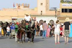 Turister som besöker Djemaa el Fna - marknadsställe i Marrakeshs den medina fjärdedelen på 24 Augusti 2014 i Marrakesh, Marocko Royaltyfria Foton