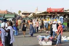 Turister som besöker Djemaa el Fna - marknadsställe i Marrakeshs den medina fjärdedelen på 24 Augusti 2014 i Marrakesh, Marocko Arkivfoton