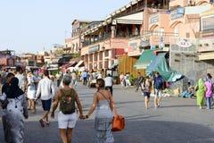 Turister som besöker Djemaa el Fna - marknadsställe i Marrakeshs den medina fjärdedelen på 24 Augusti 2014 i Marrakesh, Marocko Fotografering för Bildbyråer