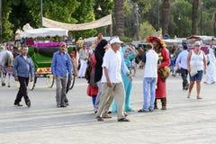 Turister som besöker Djemaa el Fna - marknadsställe i Marrakeshs den medina fjärdedelen på 24 Augusti 2014 i Marrakesh, Marocko Royaltyfri Bild
