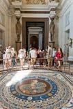 Turister som besöker en av korridorerna av Vaticanenmuseerna i ROM-minne Arkivfoton