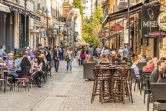 Turister som besöker och har lunch på det utomhus- restaurangkafét Arkivfoton