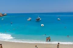 Turister som besöker stranden av byn av Agios Nikitas, Lefkada, Ionian öar, Gree arkivfoto