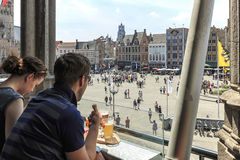 Turister som dricker öl och äter choklad, medan tycka om en panoramautsikt av marknadsfyrkanten i mitten av Bruges, mördegstårta Arkivbilder