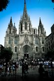 Turister som förbigår en gotisk katolsk kyrka Arkivfoto
