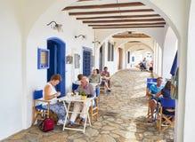 Turister som förnyar på terrassen av en krog i ett galleri av Calella de Palafrugell spain arkivbilder