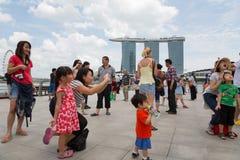 Turister som fotograferas mot bakgrunden av Singapore Fotografering för Bildbyråer