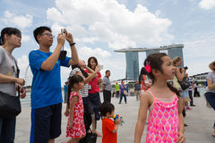 Turister som fotograferas mot bakgrunden av Singapore Royaltyfria Bilder