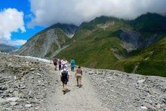 Turister som fotvandrar in mot rävglaciären, södra ö, Nya Zeeland royaltyfri fotografi