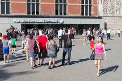 Turister som framme går av centralstationen av Amsterdam Royaltyfri Foto