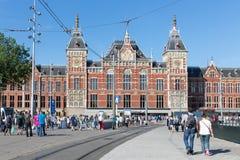 Turister som framme går av centralstationen av Amsterdam Royaltyfria Bilder
