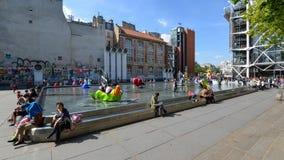 Turister som framme går av den Stravinsky springbrunnen Arkivfoto