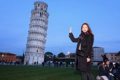 Turister som framme poserar av det lutande tornet av Pisa ledare Arkivfoton
