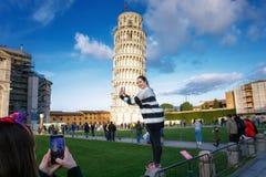 Turister som framme poserar av det lutande tornet av Pisa ledare Arkivbilder