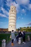 Turister som framme poserar av det lutande tornet av Pisa ledare Arkivbild