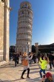 Turister som framme poserar av det lutande tornet av Pisa ledare Fotografering för Bildbyråer