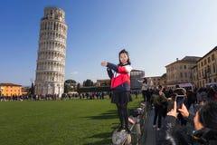 Turister som framme poserar av det lutande tornet av Pisa ledare Royaltyfria Bilder