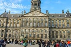 Turister som går bredvid Royal Palace i Amsterdam, Netherlaen Fotografering för Bildbyråer
