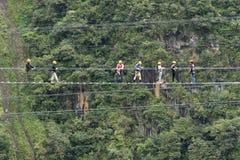 Turister som går en inställd kabelbro i Ecuador Arkivbild